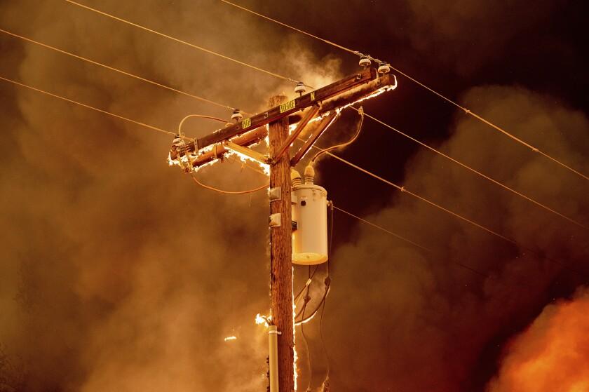Fire burns along a power pole at night