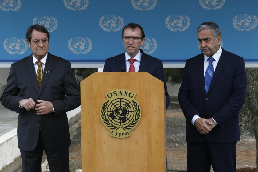 Cyprus president Nicos Anastasiades, left, and Turkish Cypriot leader Mustafa Akinci, right, stand by the United Nations envoy Espen Barth Eide during a statement to the media after their meeting at the UN-controlled abandoned Nicosia airport on the divided island of Cyprus, Wednesday, Nov. 25, 2015. Eide says intensified talks aimed at reunifying ethnically divided Cyprus have yielded further progress and that the island's rival leaders are confident remaining issues can be resolved soon. (AP Photo/Petros Karadjias)