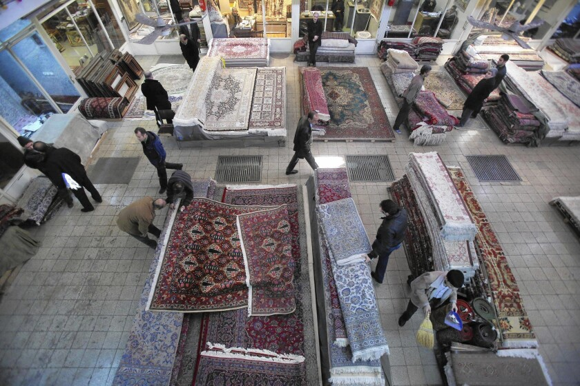 Iranian merchants and customers move among the stacks of carpets at a shop in Tehran's main bazaar. With the election last year of President Hassan Rouhani, a moderate keen to lure foreign capital, many business owners envision an Iran restored to its pre-Islamic Revolution role as a strategically situated magnet for world trade.
