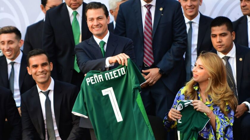 Mexican President Enrique Peña Nieto, center, with Mexican soccer star Rafael Marquez, left, who is accused by the U.S. Treasury Department of aiding a drug kingpin.