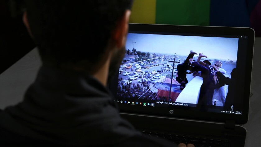 In this Oct. 22, 2015, file photo, Daniel Halaby, a gay Syrian living in southern Turkey, shows a photo from his laptop of Islamic State group militants throwing a man off a roof for allegedly violating the extremists' ban on homosexuality.