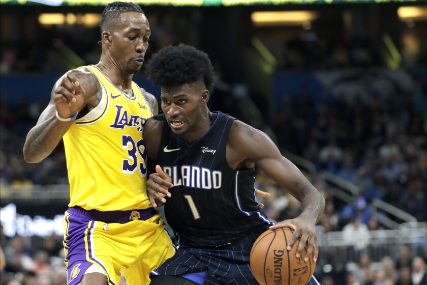 Magic forward Jonathan Isaac (1) looks for a path to the basket against Lakers center Dwight Howard during the second half of a game Dec. 11, 2019, in Orlando.