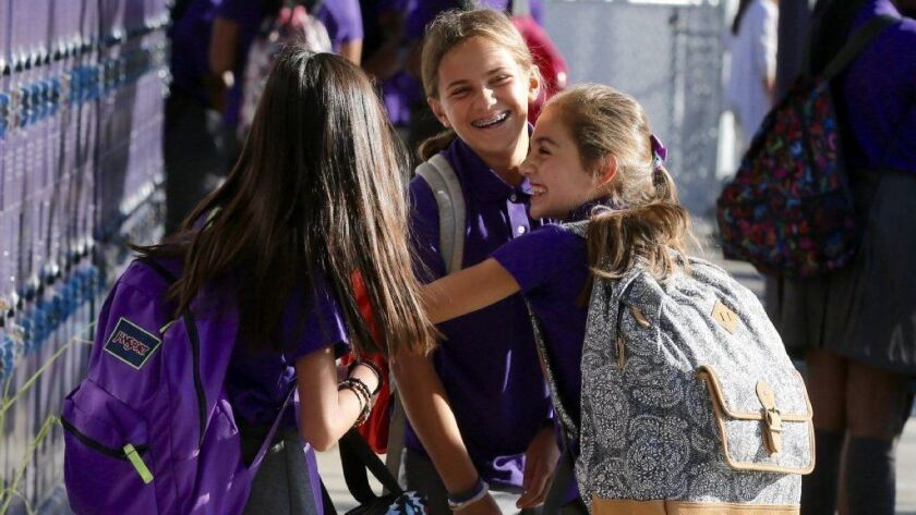 Leila Shiva, right, greets her friends Delia Mizrahi, center, and Alexis Escuadro on first day of classes at the Girls Academic Leadership Academy in Los Angeles in 2016. Now the school is being renamed after retiring Supt. Michelle King.