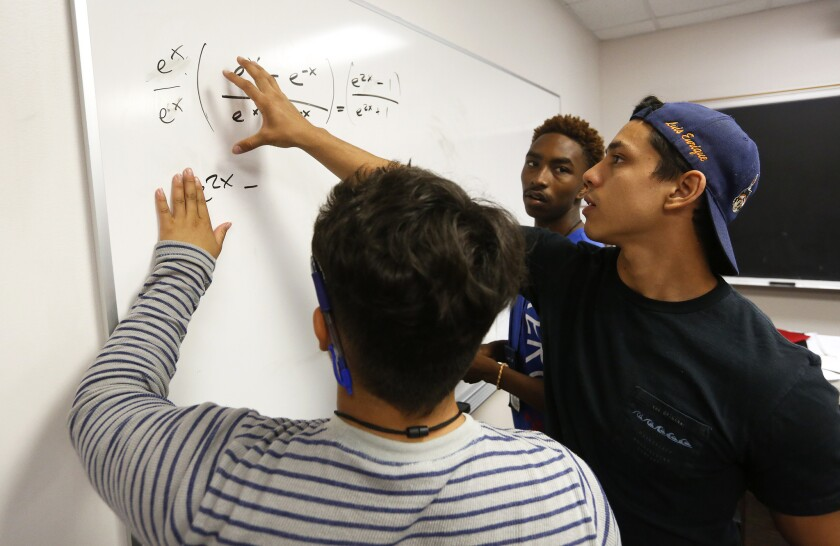 Teacher's assistant Alejandro Fernandez, right, helps Carlos Rivas, 17, left, and David-Earl Russell, 17, with a precalculus equation as part of the college-prep South Central Scholars Summer Academy at USC.