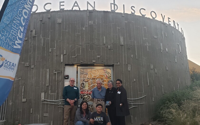 John and Dina Johns bookend artist James Hubbell and Mary Coakley Munk in front of the Ocean Discovery Institute's new Currents gate — accompanied by students of the City Heights facility.