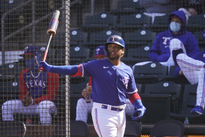 Texas Rangers' Willie Calhoun warms up before batting in the fourth inning of a spring training baseball game against the San Diego Padres, Thursday, March 4, 2021, in Surprise, Ariz. Calhoun, who got hit in the face by a fastball in a 2020 spring training game says he no longer feels like flinching or bailing out on breaking pitches. (AP Photo/Sue Ogrocki)