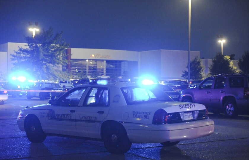 Police surround the Grand Theatre in Lafayette, La., after a shooting there Thursday night. Two moviegoers were killed and nine were injured.