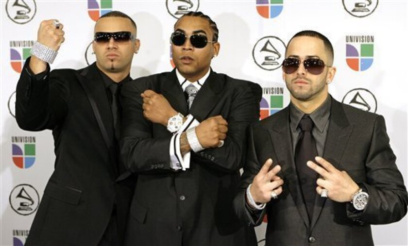 FILE - In this Nov. 2, 2006 file photo, Yandel, left, Don Omar, center and Wisin arrive for the Latin Grammy Awards in New York. The popular Puerto Rican reggaeton duo of Wisin and Yandel is breaking up. Accompanied by Yandel, reggaeton singer Don Omar made the announcement late Friday, May 3, 2013 at a concert in the U.S. territory as he praised Yandel's future as a soloist. Yandel's real name is Llandel Veguilla Malave, and his singing partner is Juan Luis Morera Luna. (AP Photo/Stuart Ramson