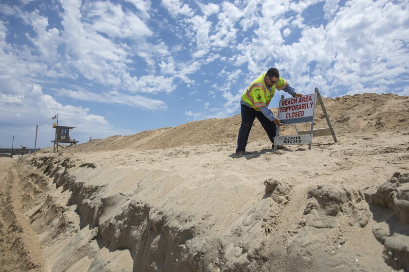 Michael Martinez with the Newport Beach Public Works Department places a sign on a sand berm near Balboa Pier.