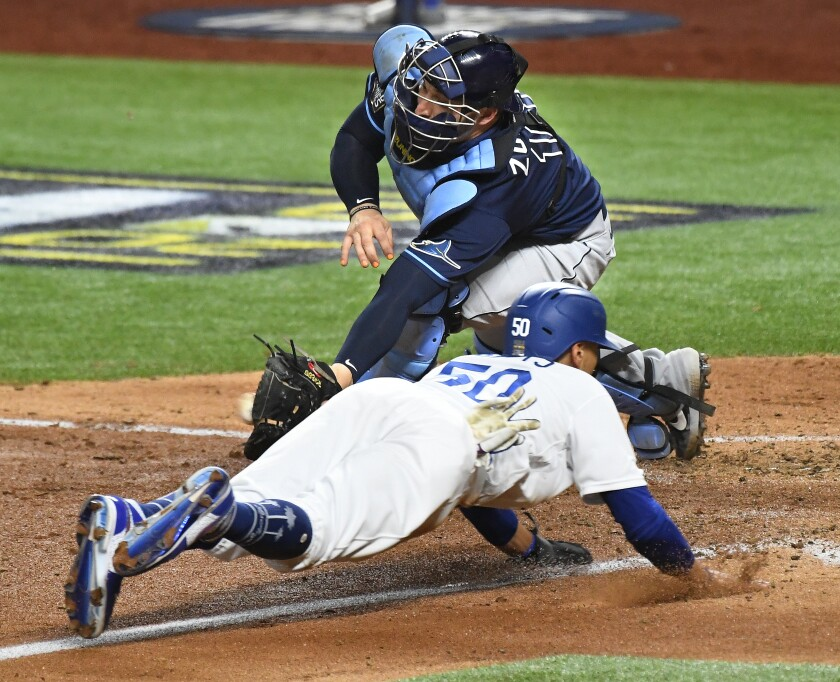 Dodgers baserunner Mookie Betts beats the tag of Rays catcher Mike Zunino to sore a run in the fifth inning.