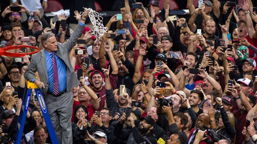 San Diego State coach Brian Dutcher shows off to fans the net he had just cut off, after the team's