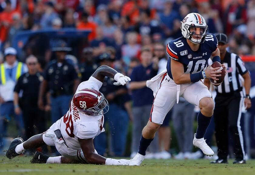 Auburn quarterback Bo Nix (10) breaks a tackle by Alabama's Christian Barmore (58) in the first half on Saturday in Auburn, Ala.