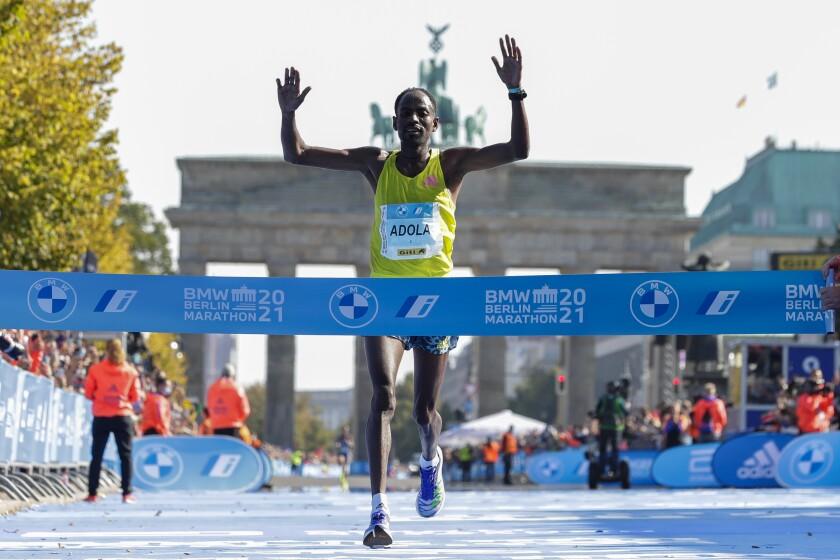 Ethiopia's Guye Adola celebrates as he crosses the finish line to win the Berlin Marathon in Berlin, Germany, Sunday, Sept. 26, 2021. (AP Photo/Lisa Leutner)