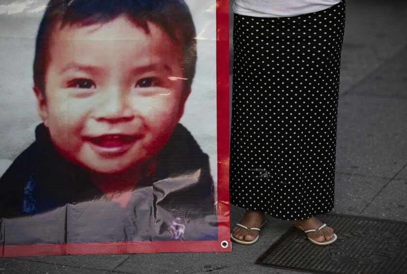 Juana Perez, whose 2 1/2 year-old son Dylan is missing, holds a poster of him outside of the presidential palace where she seeks help from President Manuel Andres Lopez Obrador to find him, in Mexico City, Wednesday, July 22, 2020. The search for Perez's boy who was led away from a market in southern Mexico's Chiapas state three weeks ago led police to a horrifying discovery: 23 abducted children being kept at a house and forced to sell trinkets in the street. Pérez said officials told her that her son had not yet been found. (AP Photo/Fernando Llano)