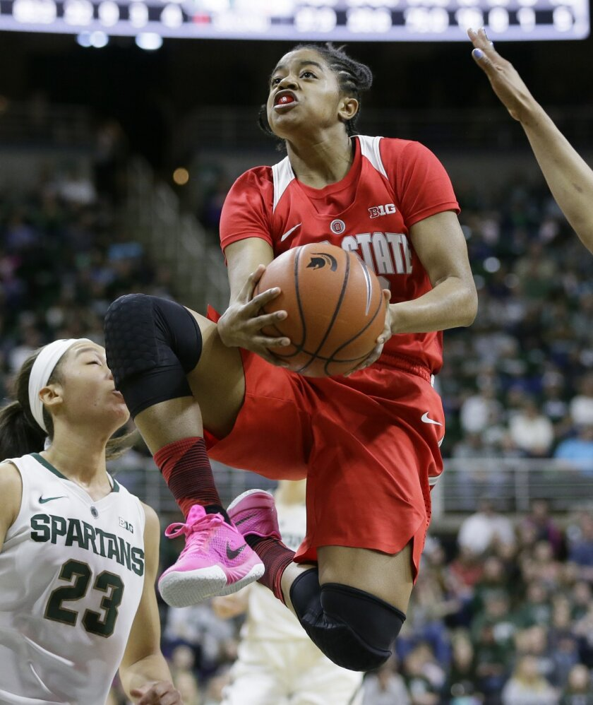 Ohio State guard Asia Doss makes a layup next to Michigan State forward Aerial Powers (23) during the first half of an NCAA college basketball game, Saturday, Feb. 27, 2016, in East Lansing, Mich. (AP Photo/Carlos Osorio)