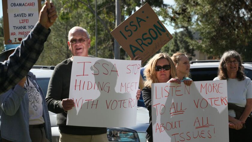 Retired U.S. Marine Tim O'Healy, left, with his wife, Misty O'Healy, joined more than 100 people gathered last Tuesday outside of Rep. Darrell Issa's Vista office. (Peggy Peattie / San Diego Union-Tribune)
