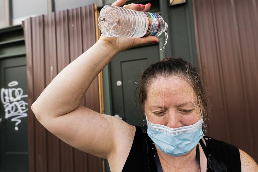 Darlene McApline dumps water on her head to cool off in Portland, Ore.