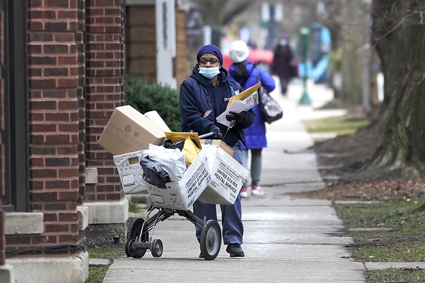 A U.S. postal worker makes deliveries in the Hyde Park neighborhood of Chicago.