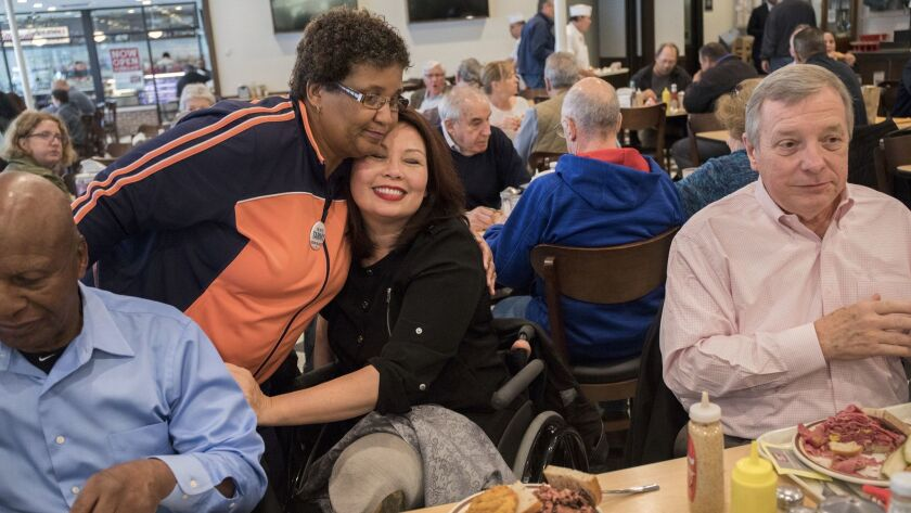 Tammy Duckworth, center, candidate for U.S. senator for Illinois, gets a hug from supporter Demetria Puckett, 62, during lunch with Secretary of State Jesse White, left, and Sen. Richard J. Durbin on Tuesday in Chicago.