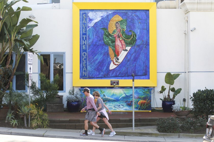 """Pedestrians walk past the """"Surfing Madonna"""" mosaic displayed on Encinitas Boulevard, near the Coast Highway intersection, on Dec. 24, 2019 in Encinitas."""
