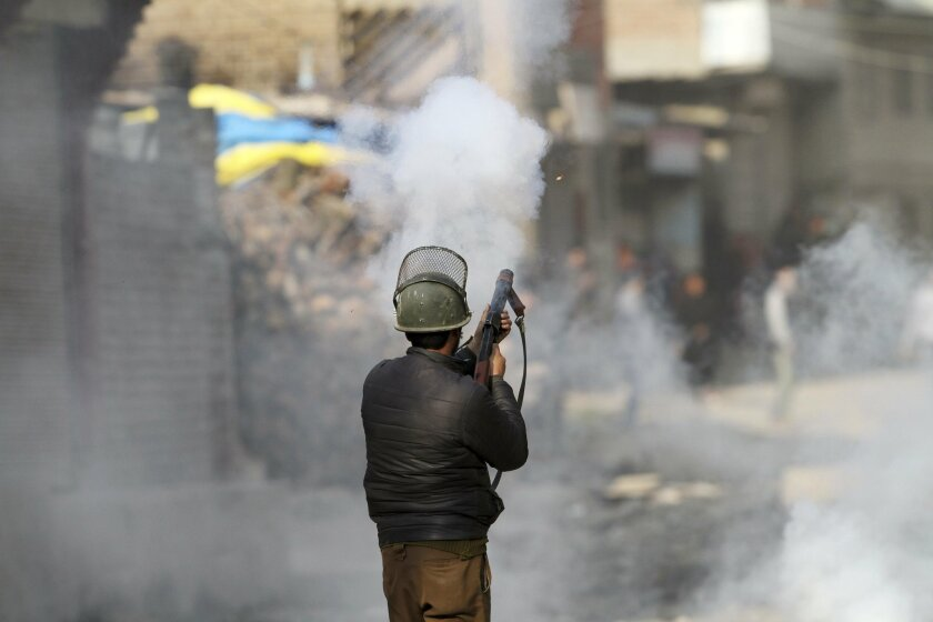 An indian policeman fires tear smoke shell on protesters during a clash in  Srinagar, Indian controlled Kashmir, Monday, Feb. 15, 2016. Authorities imposed a curfew in some parts of Indian-controlled Kashmir on Monday amid a general strike called by separatist groups to protest the killing of a tee