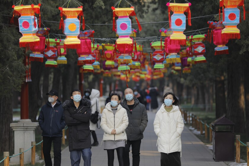 People wear masks in Jingshan Park in Beijing. Beijing canceled many Spring Festival celebrations because of the coronavirus outbreak.