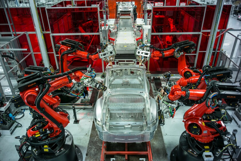 Robots build Teslas at a factory in Fremont, Calif.