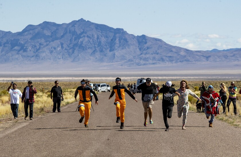 Alien enthusiasts Naruto run toward the back gate of Area 51