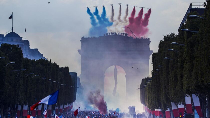 The 'Patrouille de France' military aircrafts pass over the Champs Elysees avenue as French supporters greet their national soccer team players during a parade down the Champs-Elysee avenue in Paris.