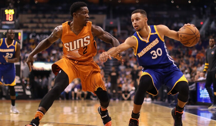 Golden State's Stephen Curry, left, handles the ball under pressure from Phoenix's Eric Bledsoe during the first half Sunday.
