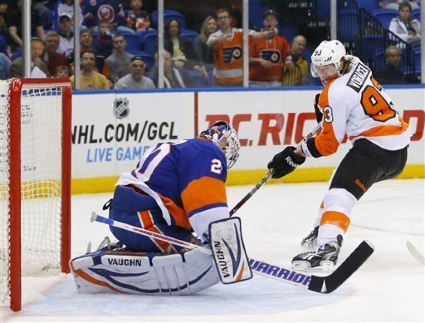 New York Islanders goalie Evgeni Nabokov (20) stops a shot by Philadelphia Flyers right wing Jakub Voracek (93) before being slid into by teammate Andrew MacDonald, not shown, causing the puck to eventually enter the net for a goal credited to Voracek during the first period of an NHL hockey game i