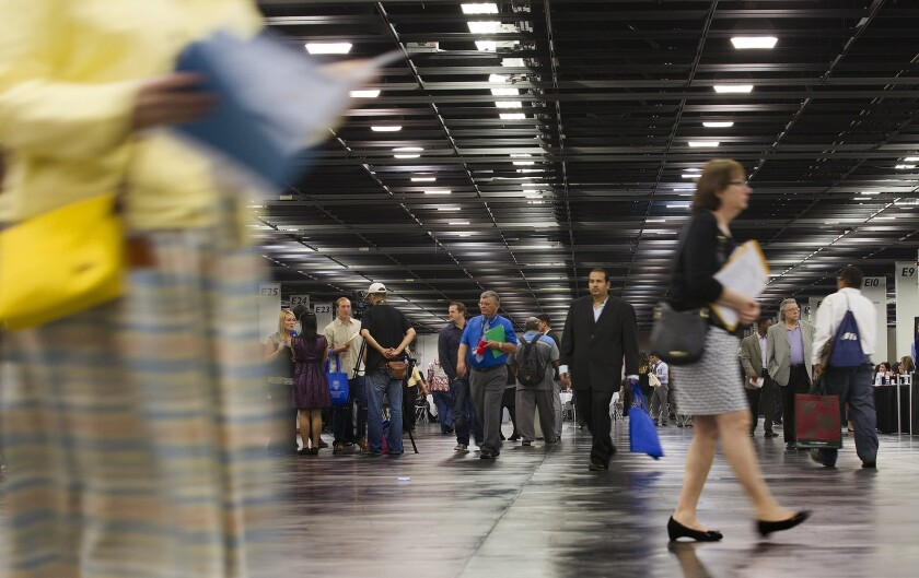 Workers in both the upper- and lower-income brackets have had their wages increase, while those in the middle have seen continued declines. Above, job seekers browse booths at a job fair in Anaheim last year.