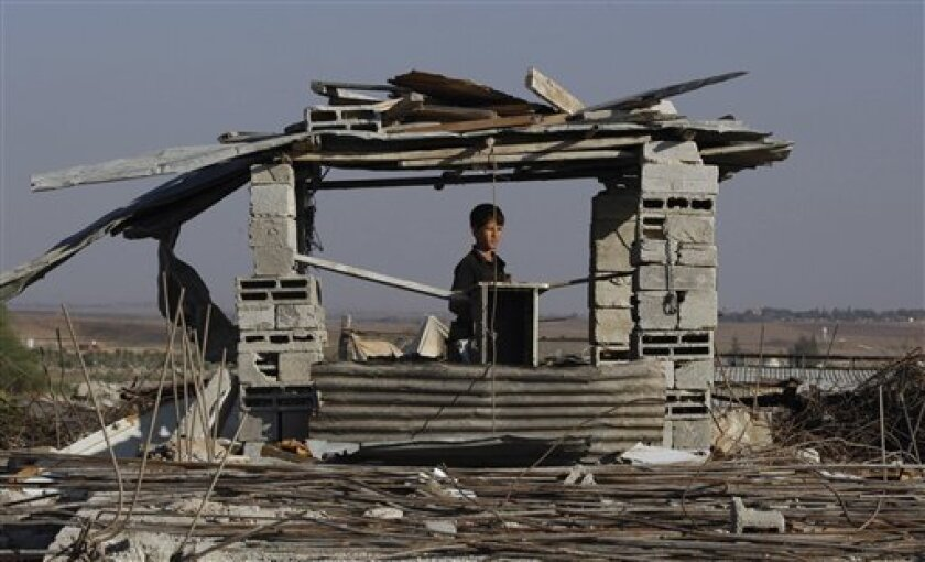 A Palestinian boy looks on as he stands on top of rubble from a building destroyed in January's Israeli military offensive, in Jebaliya, northern Gaza Strip,Tuesday, Sept. 29, 2009. A U.N. investigator defended a report Tuesday that accuses Israel and Palestinian militants of war crimes during their conflict in Gaza, an allegation Israel condemns and claims is the result of bias against the Jewish state. Former South African Judge Richard Goldstone said he and his fellow investigators rejected criticism by Israel that the 575-page report was politically motivated. (AP Photo/Hatem Moussa)