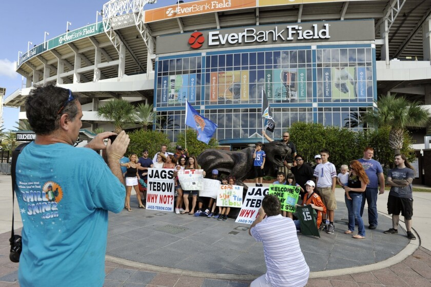 Jon Durst, left, takes a group photo of fans during a rally Monday at EverBank Field to encourage the Jacksonville Jaguars to sign Tim Tebow.
