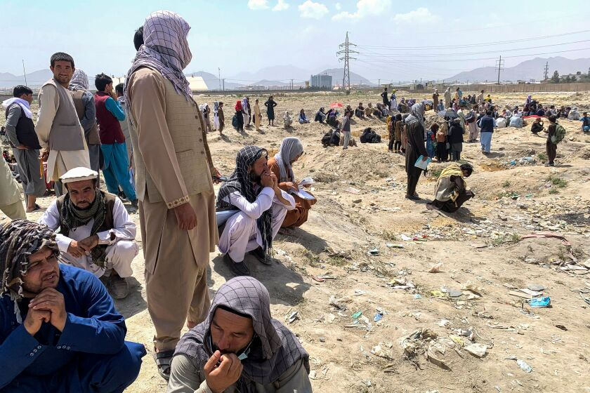 Afghan people gather as they wait to board a U.S. military aircraft to leave the country