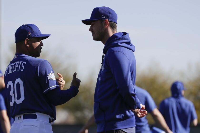 Dodgers manager Dave Roberts, left, talks with center fielder Cody Bellinger at spring training in Glendale, Ariz.