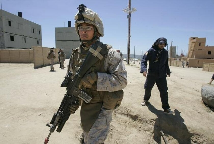 Marine Lance Cpl. Henry Miel patrols a mock Afghan village. At right is a man playing the role of an Afghan police officer.