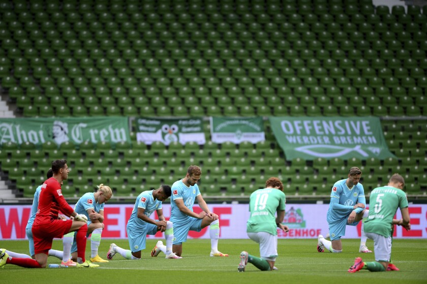 Players of both teams kneel together on the grass at the centre circle to send a signal against racism prior to the German Bundesliga soccer match between Werder Bremen and VfL Wolfsburg in Bremen, Germany, Sunday, June 7, 2020. (Patrick Stollarz, Pool via AP)