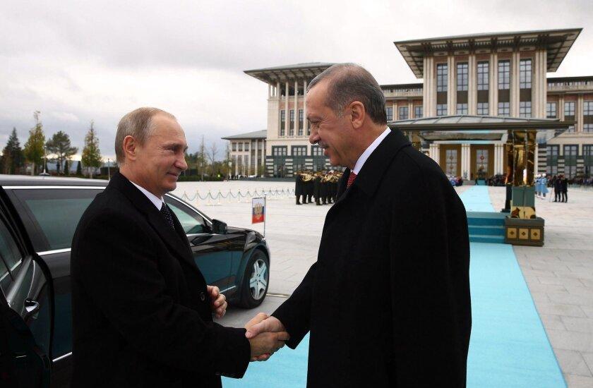 Turkish President Recep Tayyip Erdogan, right, welcomes Russian President Vladimir Putin at the presidential palace in Ankara on Monday.