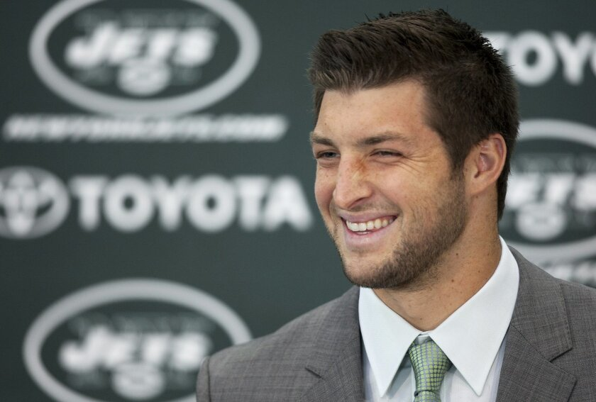 FILE - Tim Tebow holds his first news conference with the New York Jets, in this March 26, 2012 file photo taken in Florham Park, N.J. Manny Pacquiao welcomed a high-profile visitor to his training camp Saturday March 21, 2015 with ties to his native Philippines: Tim Tebow. (AP Photo/Mark Lennihan,