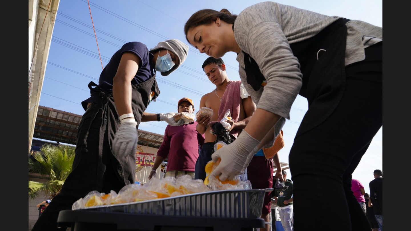 Gisell Cuen (right) from World Central Kitchen along with a volunteer pass out sandwiches and orange slices for lunch at El Barretal migrant shelter in Tijuana.