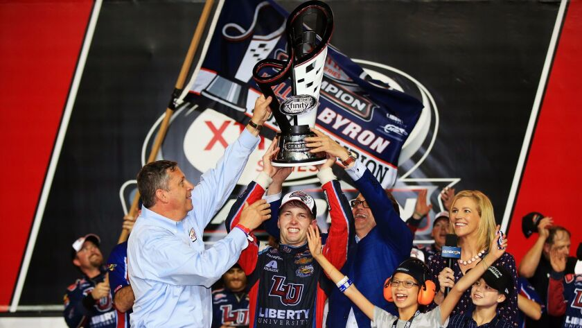 William Byron, driver of the #9 Liberty University Chevrolet, celebrates with the trophy in Victory Lane after placing third and winning the NASCAR XFINITY Series championship.