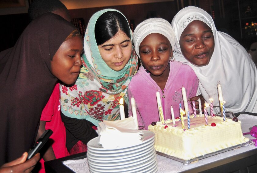 """Pakistani schoolgirl activist Malala Yousafzai, second from the left, blows out candles with Nigerians from the """"Bring Back Our Girls"""" campaign during a dinner Saturday in Abuja, Nigeria."""