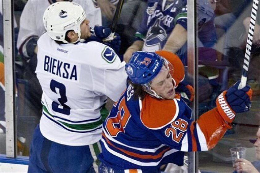 Vancouver Canucks' Kevin Bieksa, left, is checked by Edmonton Oilers' Ryan Jones during the second period of an NHL hockey game in Edmonton, Alberta, on Saturday, March 30, 2013. (AP Photo/The Canadian Press, Jason Franson)