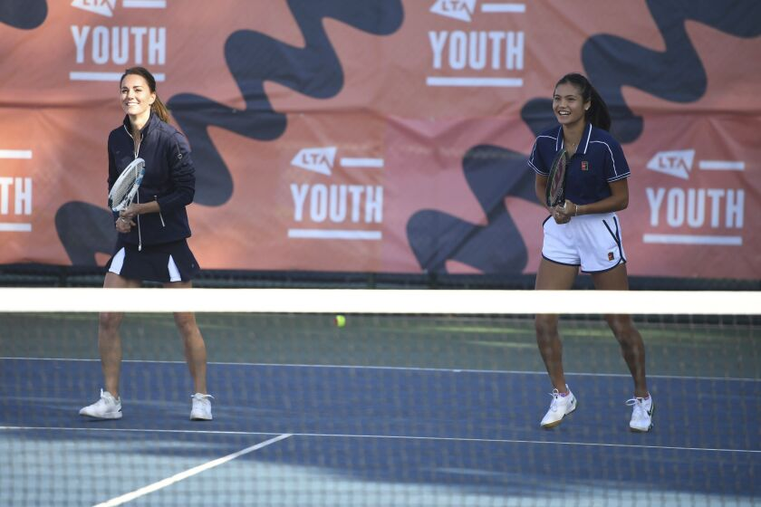 Britain's Kate, the Duchess of Cambridge, left, reacts as she plays with US Open Champion Emma Raducanu during an event hosted by the LTA Youth programme, at the National Tennis Centre in London, Friday, Sept. 24, 2021. (Jeremy Selwyn/Pool Photo via AP)