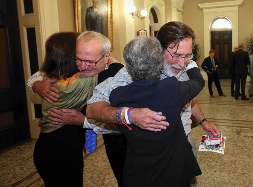 Richard Martinez, right, and Robert Weiss, second from left, who each lost a child in the Isla Vista shooting rampage in May, celebrate the state Senate's approval of a bill tightening gun laws with Assemblywoman Nancy Skinner, left, and Sen. Hannah-Beth Jackson.
