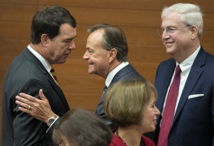 New USC Athletic Director Mike Bohn, left, chats with Rick Caruso, Chair of the USC Board of Trustees, center, following a news conference on Nov. 7.