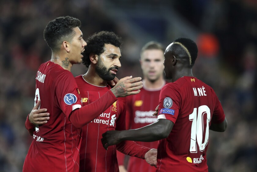 Liverpool's Mohamed Salah, second left, celebrates with teammates after scoring his side's third goal during the Champions League group E soccer match between Liverpool and Red Bull Salzburg at Anfield stadium in Liverpool, England, Wednesday, Oct. 2, 2019. (AP Photo/Jon Super)