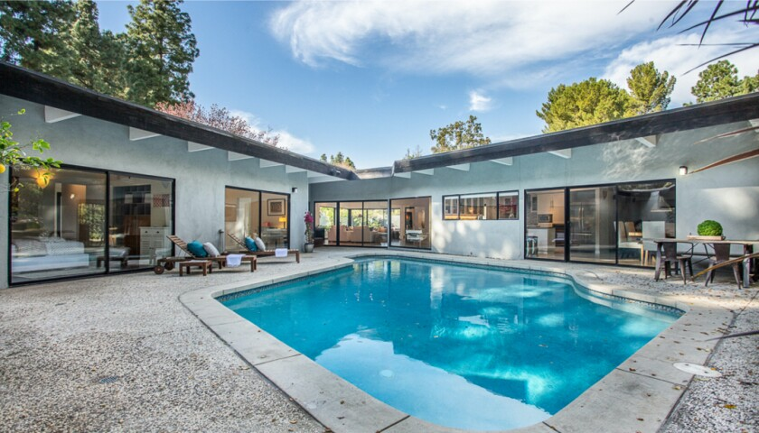 The single-story home features a spacious open floor plan and a swimming pool surrounded by privacy walls.