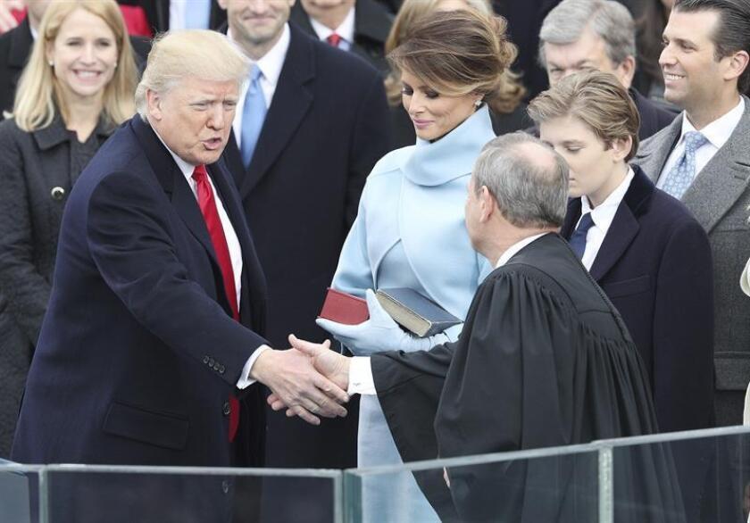 El presidente electo de EE.UU., Donald Trump (i) estrecha la mano del presidente de la Corte Suprema de Estados Unidos, John Roberts, tras prestar juramento como el presidente número 45 de la historia de Estados Unidos en una ceremonia oficial celebrada ante las escalinatas del Capitolio, en Washington DC (Estados Unidos) hoy, 20 de enero de 2017. En la foto, junto a Trump, su esposa Melania y su hijo Barron Trump. EFE